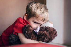 Upset child hugging a teddy bear.
