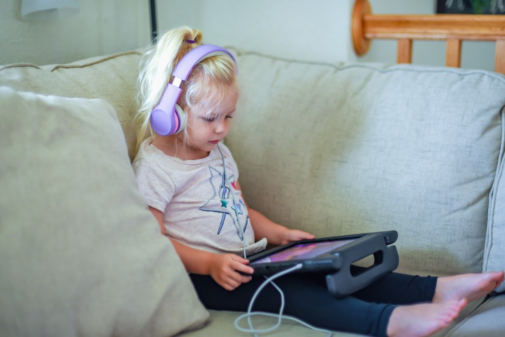 Child plays on tablet.